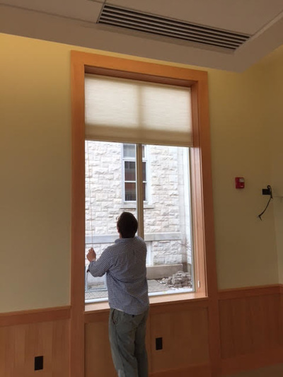 person looking up at a window shade pulled up over a large window
